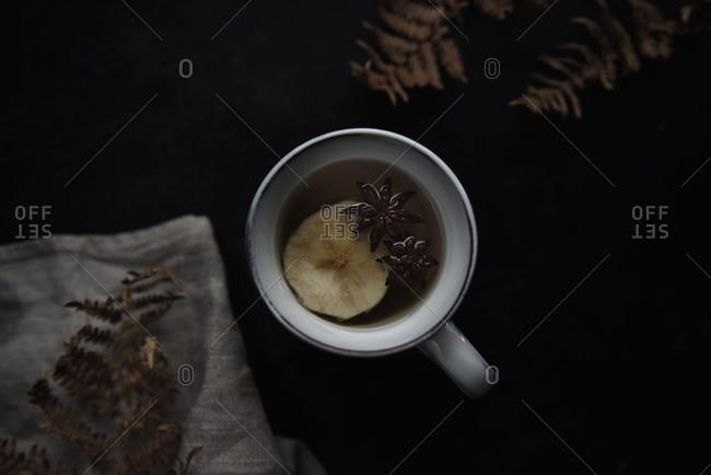 Overhead view of apple tea in mug on black table