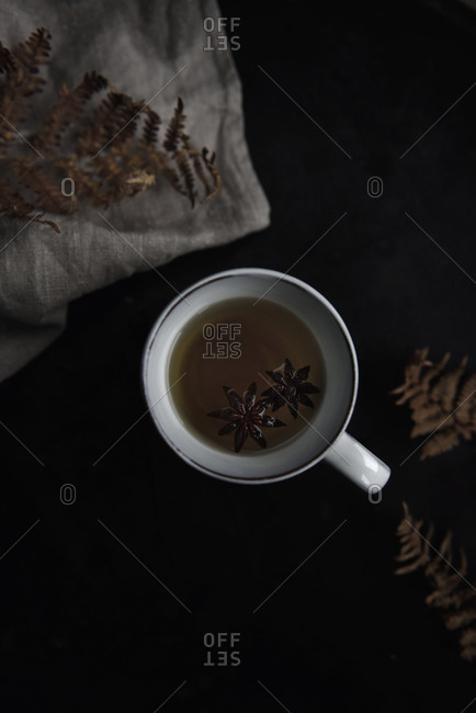 Apple tea in mug on black table viewed from above