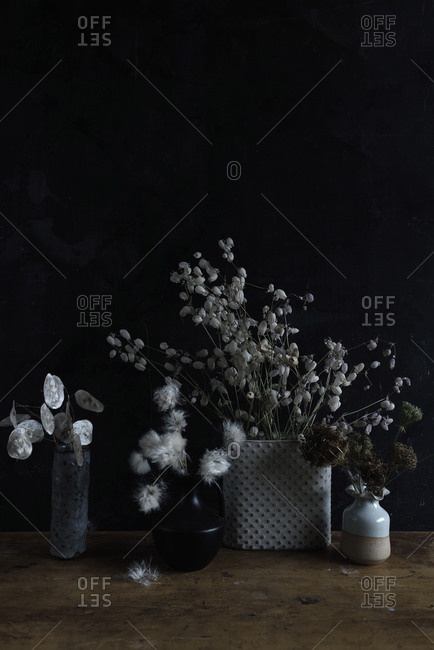 Dried flowers in vases on wooden table