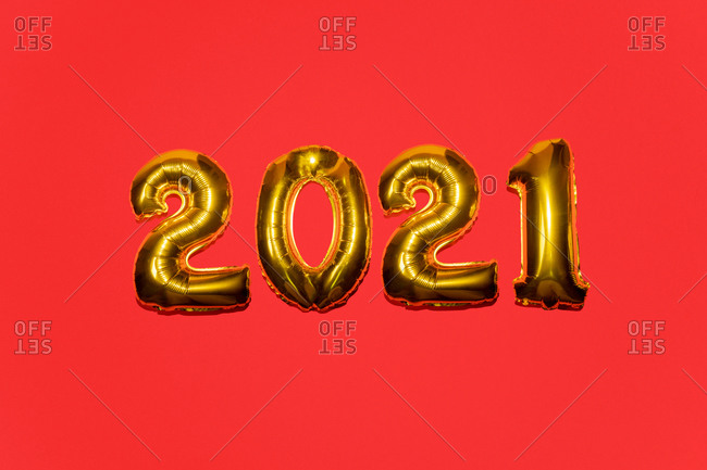 Gold mylar balloon numbers for the year 2021 on red background