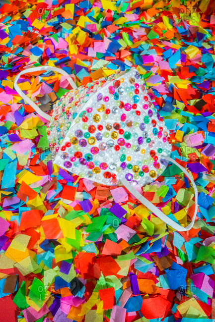 Protective mask covered in sequins and surrounded by confetti