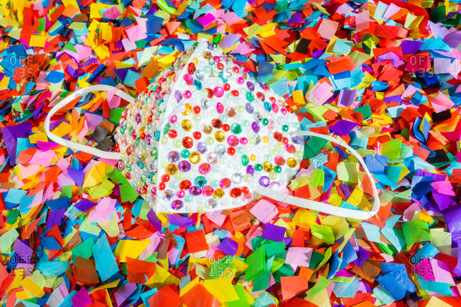 Close-up of personal protective mask with sequin decoration on colorful confetti