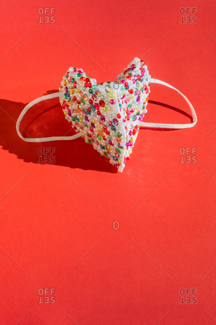 Colorful sequin mask on red background