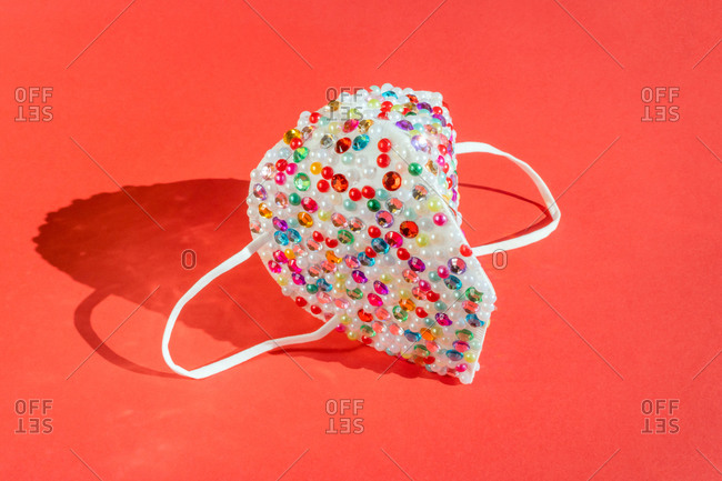 Festive sequined mask on red background
