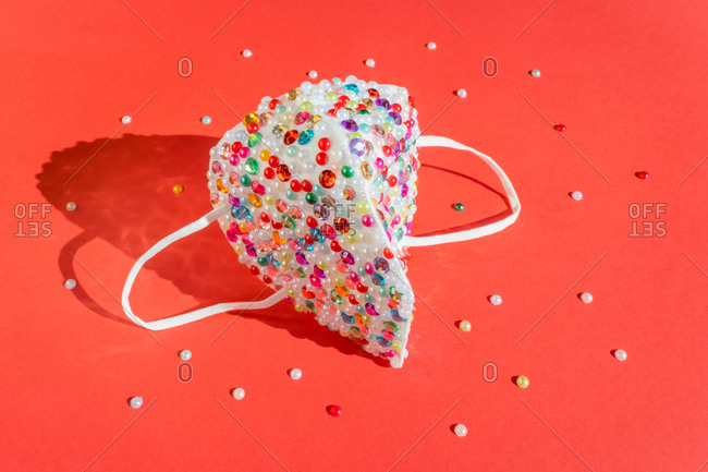 Sequin covered mask on red background with pearls