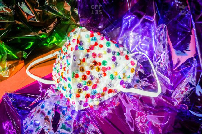 Sequin covered face mask on colorful plastic
