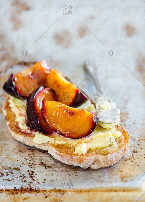 Sandwich with goat cheese, baked plum and honey on metal background