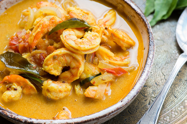 Close up of spicy shrimp curry with coconut milk and chili in bowl