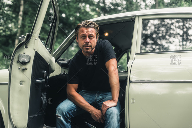 Portrait of a man sitting in retro car