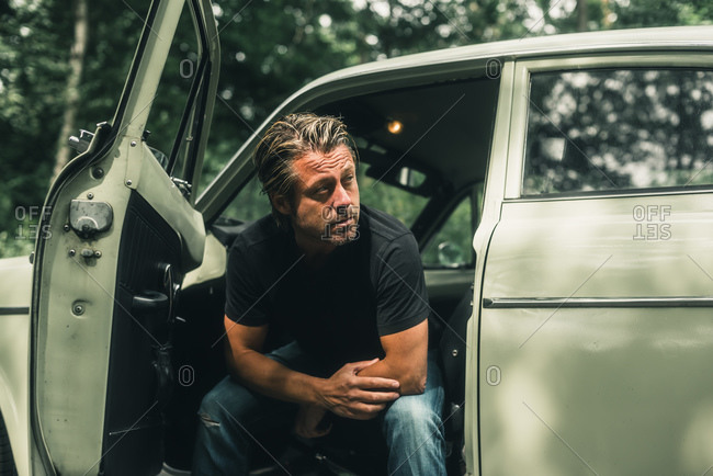 Man sitting in retro car looking away