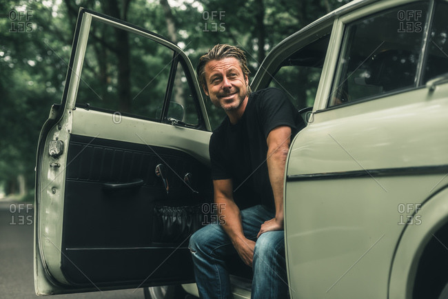 Portrait of a smiling man sitting in retro car