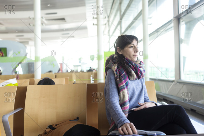 Pretty, young woman waiting at a gate area of a modern airport