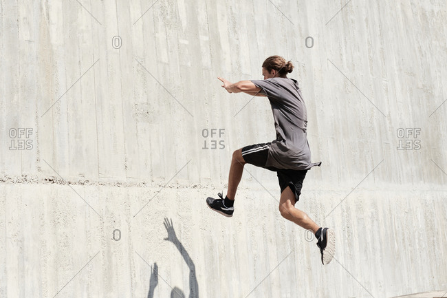 Side view of courageous young male jumping on concrete wall of building while performing dangerous stunt and doing parkour in city