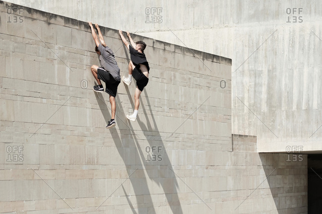 Side view of brave male friends hanging on wall of concrete building while performing risky trick and doing parkour in city