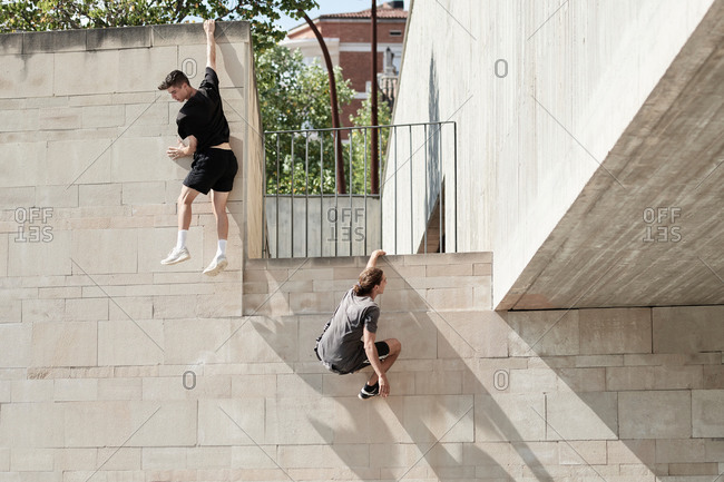 Back view of brave male friends hanging on wall of concrete building while performing risky trick and doing parkour in city