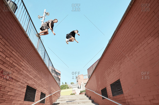 From below side view of strong males doing parkour and jumping from metal railing on brick building while showing stunts in city