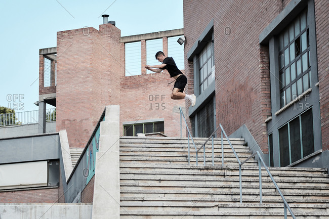 Side view of focused young male jumping over stone steps in city while doing parkour and showing trick