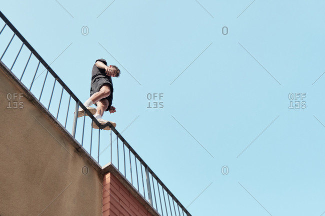 From below of male standing on metal railing of building and preparing for performing parkour trick