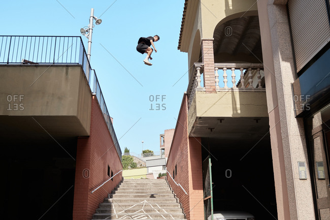 From below side view of strong male doing parkour and jumping from metal railing on brick building while showing stunts in city
