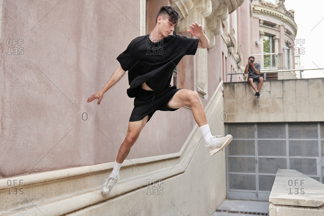 Side view of concentrated male jumping over stone fence and balancing on arm while performing stunt and doing parkour