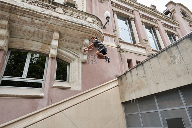 Focused young male jumping over stone steps in city while doing parkour and showing trick