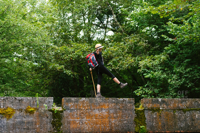 Side view of unrecognizable relaxed female tourist with backpack crossing calm river while walking along stone fence with outstretched arms