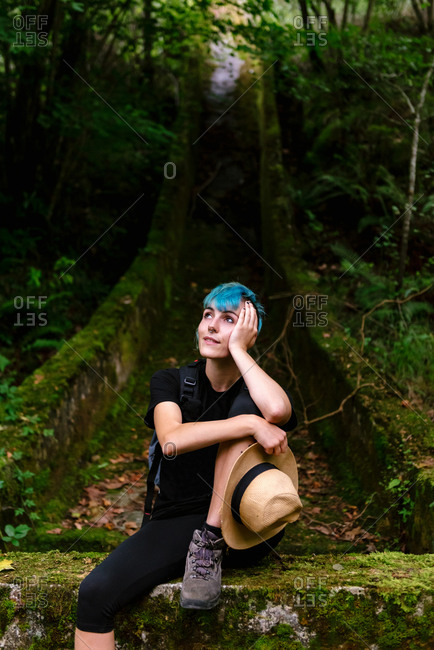 Relaxed traveling female with blue hair sitting in mossy woods during vacation and dreaming while looking up