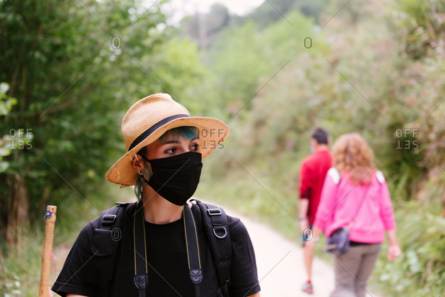 Traveling woman wearing protective mask walking along road in woods and looking away during summer holiday