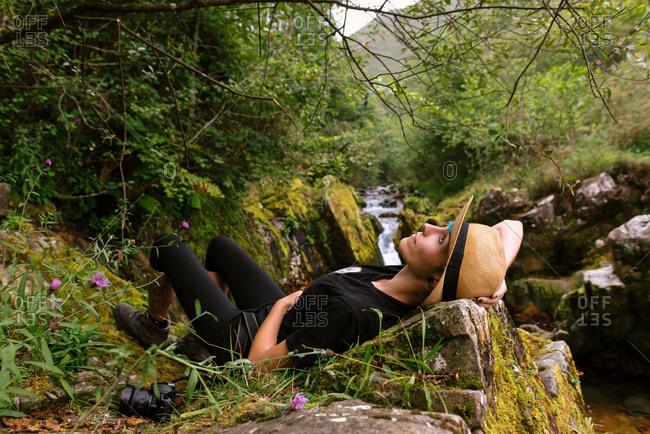 Side view of peaceful female tourist lying on stone in highland area and enjoying freedom during summer vacation