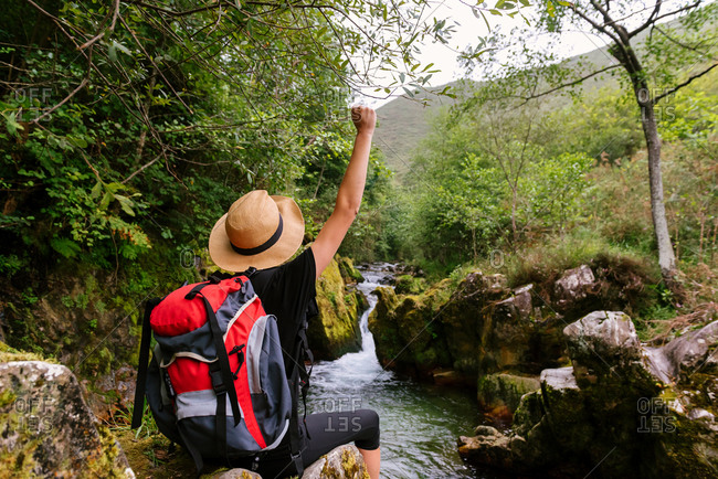 Back view of unrecognizable hiker with backpack celebrating goal achievement with fist up while standing near mountain river in woods