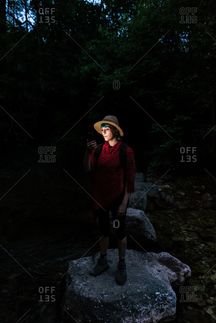Female tourist standing on rock in woods at night and searching for route while using digital map on cellphone