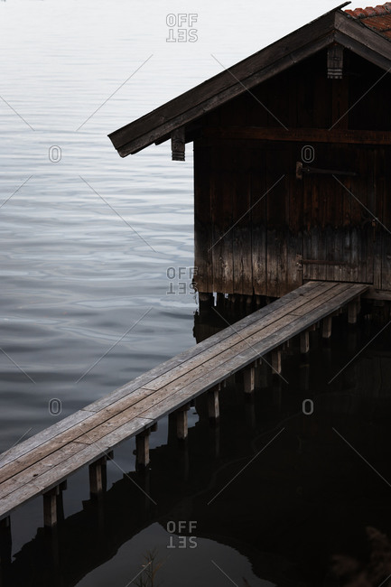High angle view of weathered wooden boat shed and plank pier over rippling dark lake water in overcast weather in autumn day
