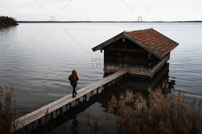 Unrecognizable female traveler in warm clothes standing on wooden plank pier near shabby shed located at lake in gloomy autumn day