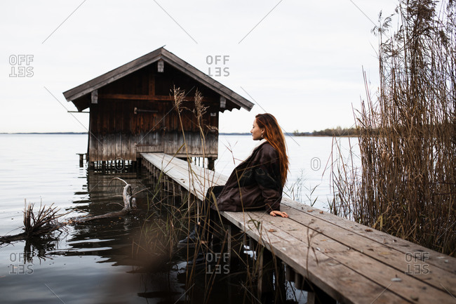 Female traveler in warm clothes sitting on wooden plank pier near shabby shed located at lake in gloomy autumn day
