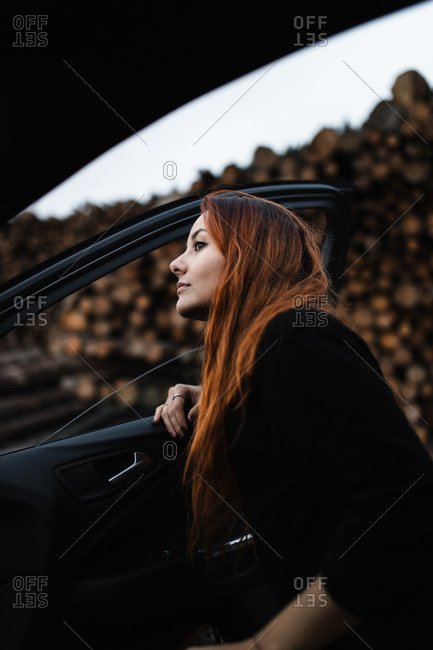 Low angle side view of young woman standing near open door of car against blurred stacked wooden logs and looking away while travelling through countryside in autumn day