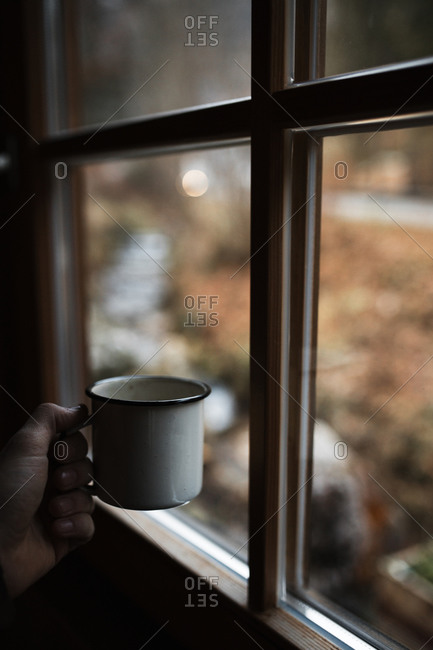 Crop unrecognizable person with enamel mug of hot coffee standing near window with blurred nature view in gloomy autumn day in countryside