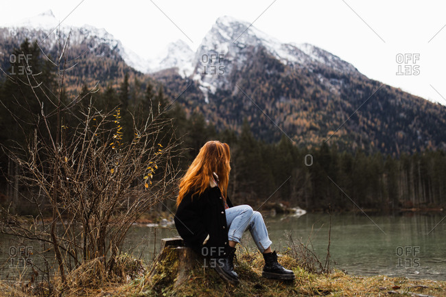 Side view of unrecognizable distant female traveler in warm outfit sitting on rocky shore of lake and observing amazing scenery of autumn forest and snowy mountains in cloudy day
