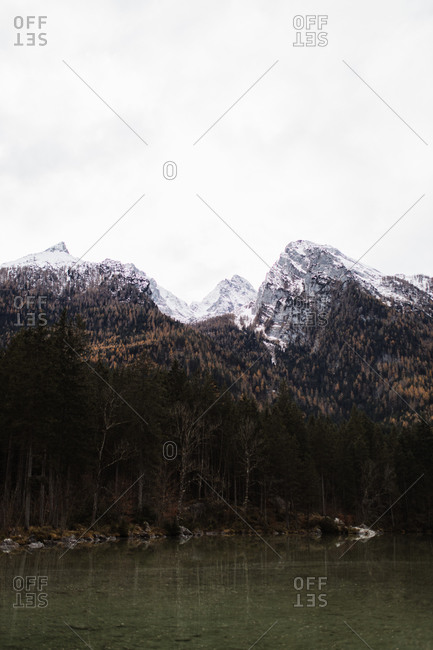Dark lake and forested mountains with snow cowered rocky peaks under gray cloudy sky in cold autumn day