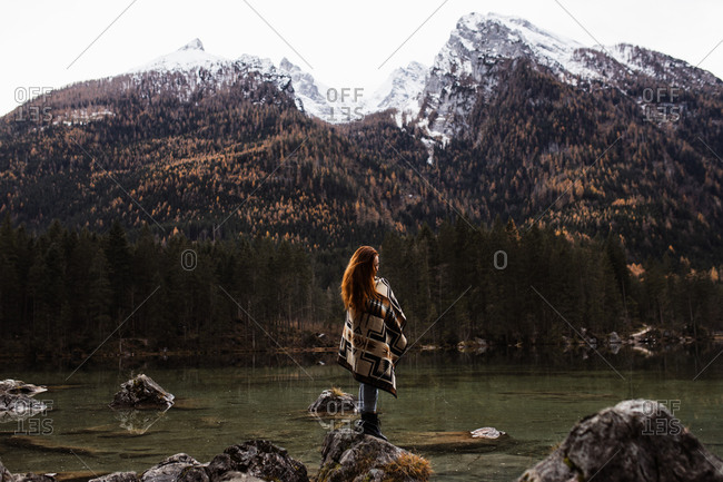 Side view of unrecognizable distant female traveler in warm outfit standing on rocky shore of lake and observing amazing scenery of autumn forest and snowy mountains in cloudy day