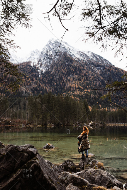 Back view of unrecognizable distant female traveler in warm outfit standing on rocky shore of lake and observing amazing scenery of autumn forest and snowy mountains in cloudy day