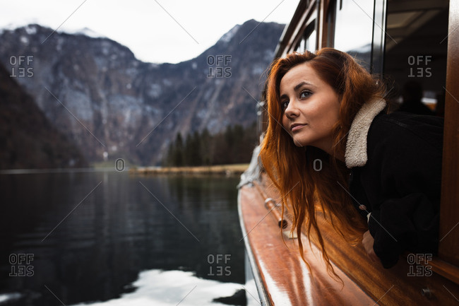 Side view of young female tourist in warm wear looking out open window while travelling by boat on calm lake surrounded by rocky mountains in autumn day