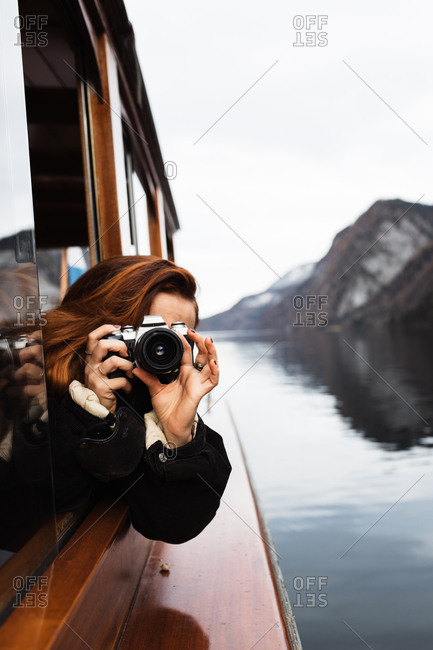 Unrecognizable female photographer in warm jacket shooting with photo camera while travelling by boat on lake with rocky shore in autumn day