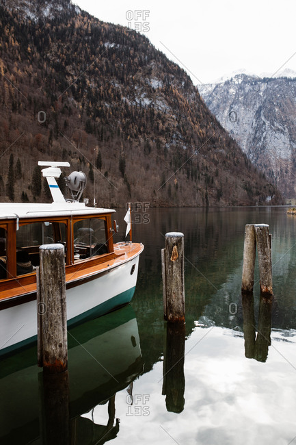 Modern motor boat moored in calm lake water surrounded by forested snowy mountains in cold autumn day