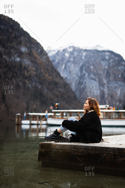 Side view of contemplative young woman in warm outerwear sitting on edge of pier near lake and admiring mountains while resting during travel in autumn day