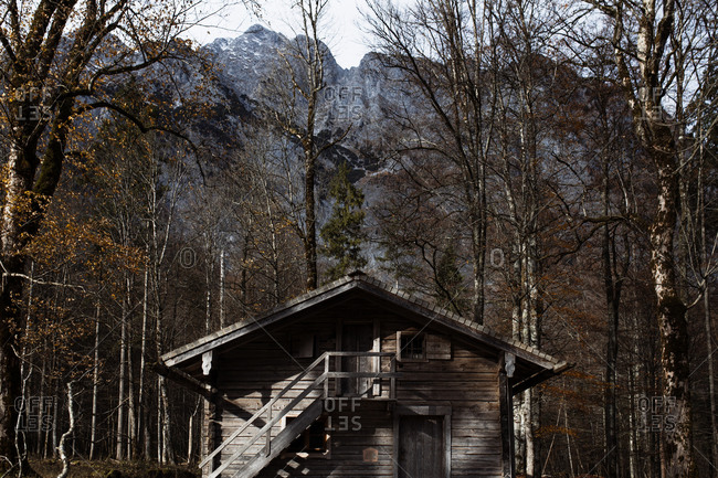 Lonely wooden house located on lake shore against rocky mountains covered with trees and snow in autumn day