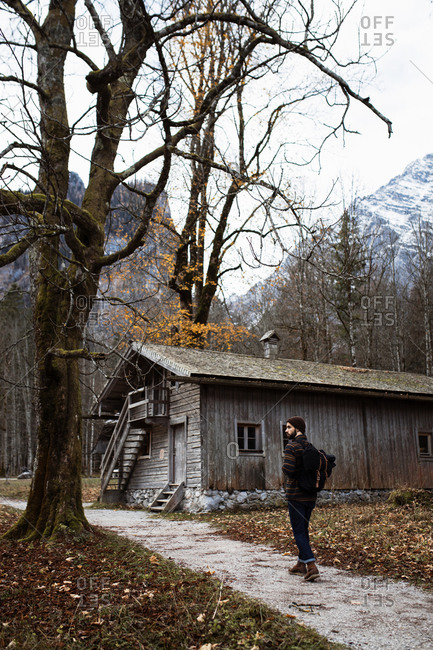 Back view of unrecognizable man in warm outerwear with backpack walking on wet pathway near old wooden hut located in leafless forest surrounded by mountains in overcast autumn day