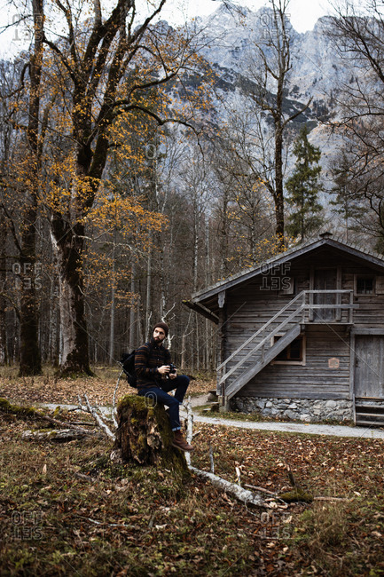 Side view of man in warm outerwear with backpack sitting on stone near old wooden hut located in leafless forest surrounded by mountains in overcast autumn day