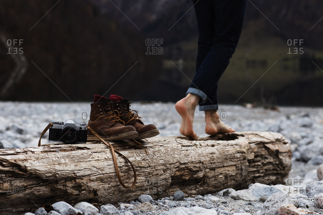 Side view of crop anonymous female traveler walking on weathered wooden log with boots and photo camera placed nearby on rocky waterfront in autumn day