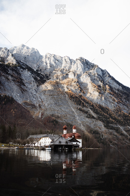Picturesque landscape with small village houses and church located on shore of calm lake against rough rocky slope of mountain covered with snow in sunny autumn weather
