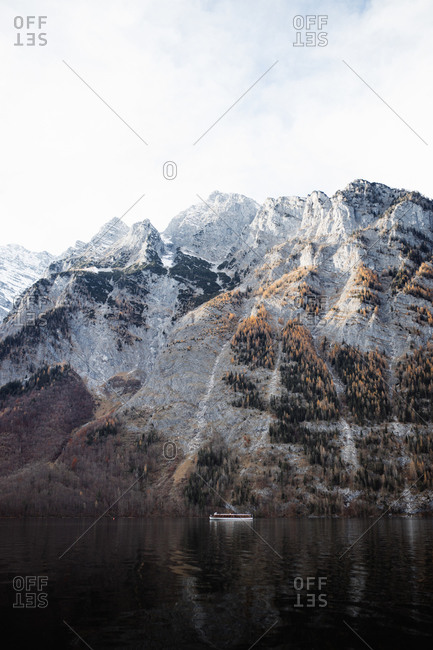 Distant motor boat floating in calm water of lake against rocky mountain covered with snow in sunny autumn day